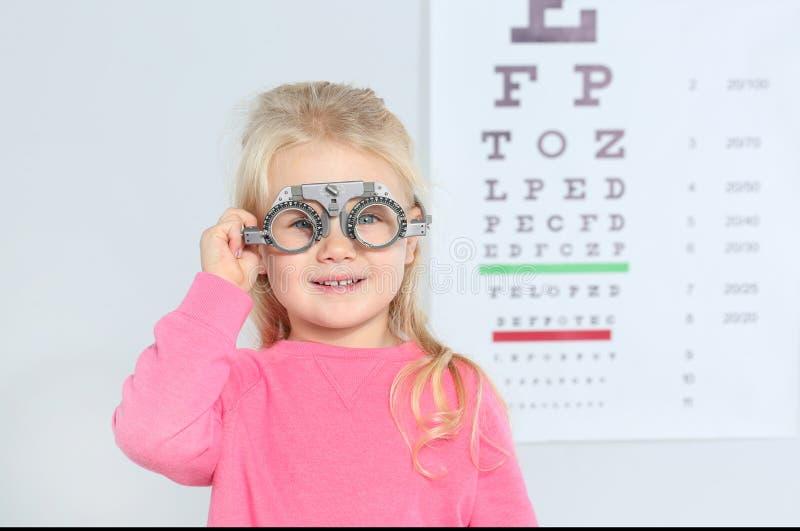 Bambina con la struttura di prova vicino al grafico di occhio in ospedale fotografia stock