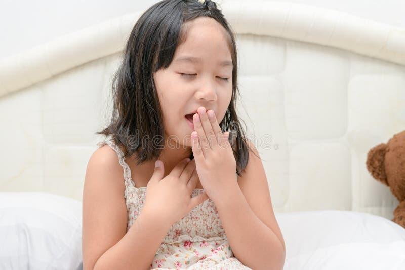 Bambina con la tosse e la gola irritata che si sentono male sul letto immagine stock