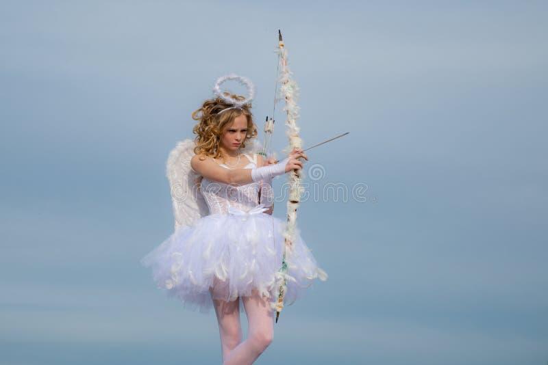 Bambina con le ali e l'alone di angelo Ali bianche d'uso del vestito e della piuma dal costume di angelo della ragazza del bambin fotografia stock