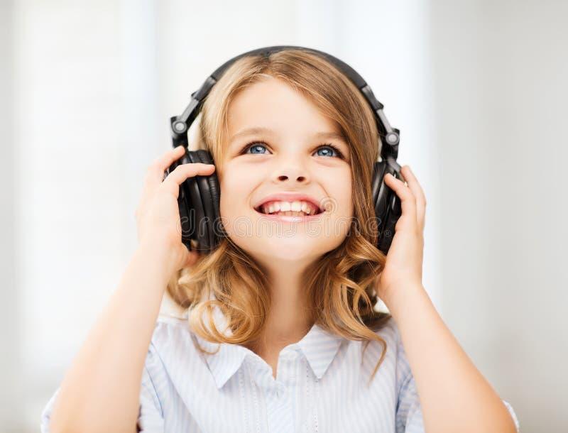 Bambina con le cuffie a casa fotografia stock libera da diritti