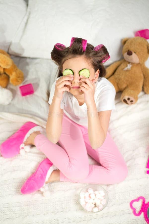 Bambina con le fette del cetriolo sui suoi occhi fotografie stock