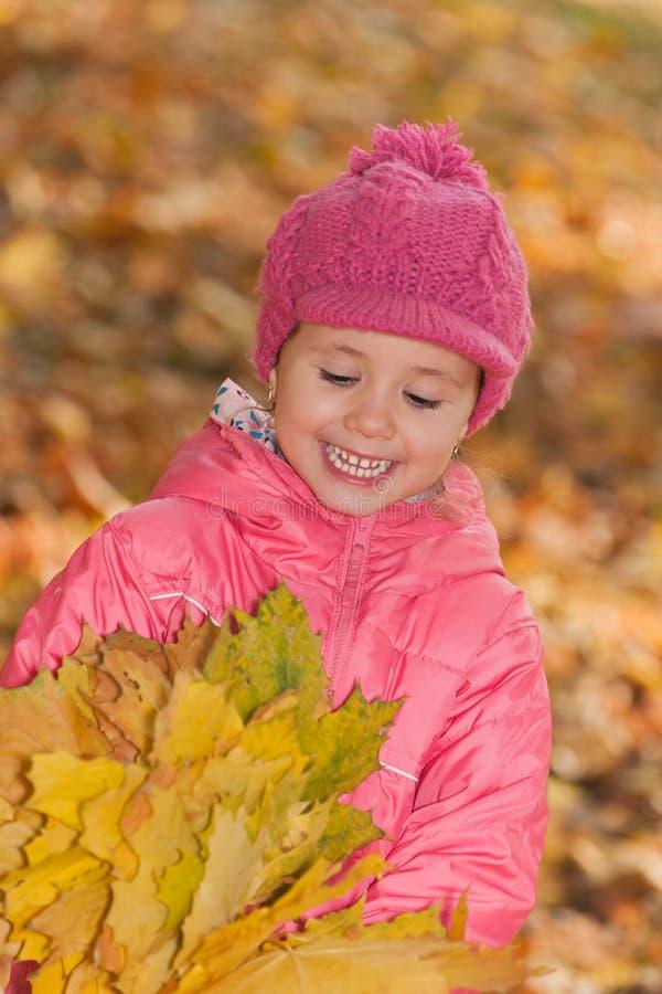 Bambina con le foglie gialle immagine stock