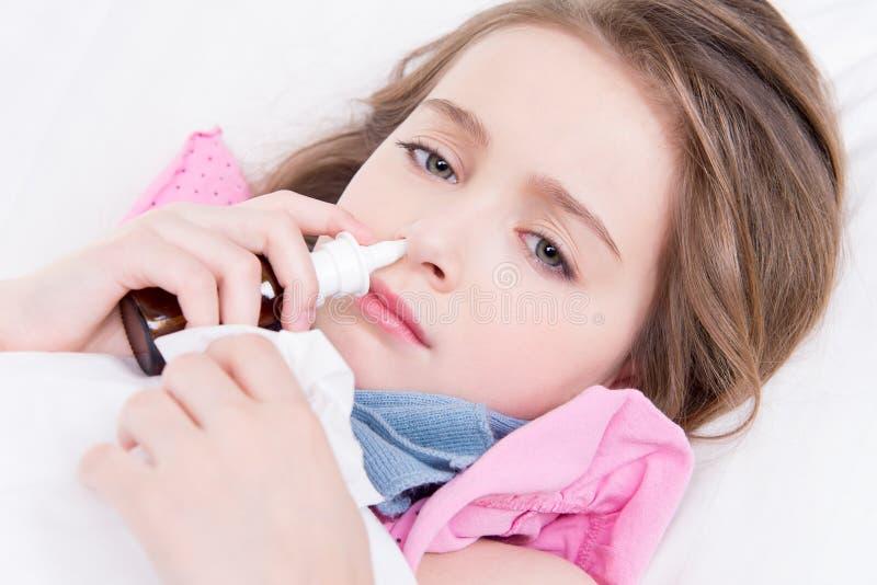 Bambina con le gocce nasali di cattiva utilizzazione del freddo. immagine stock libera da diritti