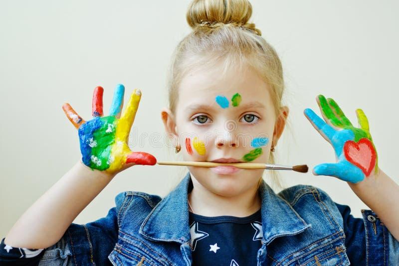 Bambina con le mani in pittura immagini stock