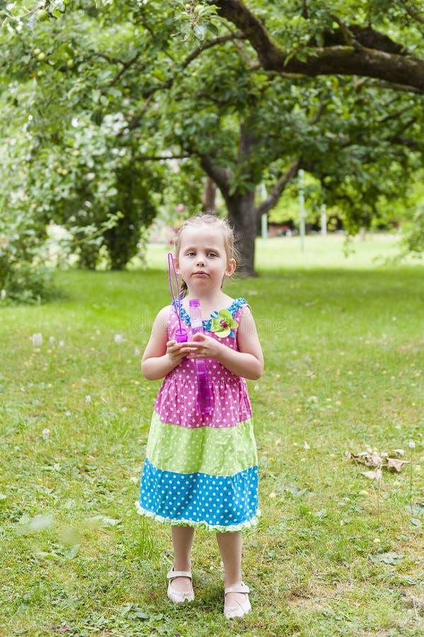 Bambina con le trecce in un vestito variopinto che sta pensively nel parco con le bolle di sapone fotografia stock libera da diritti