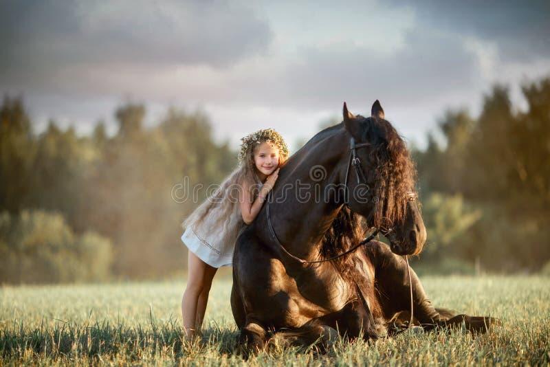 Bambina con lo stallone frisone nero fotografia stock libera da diritti