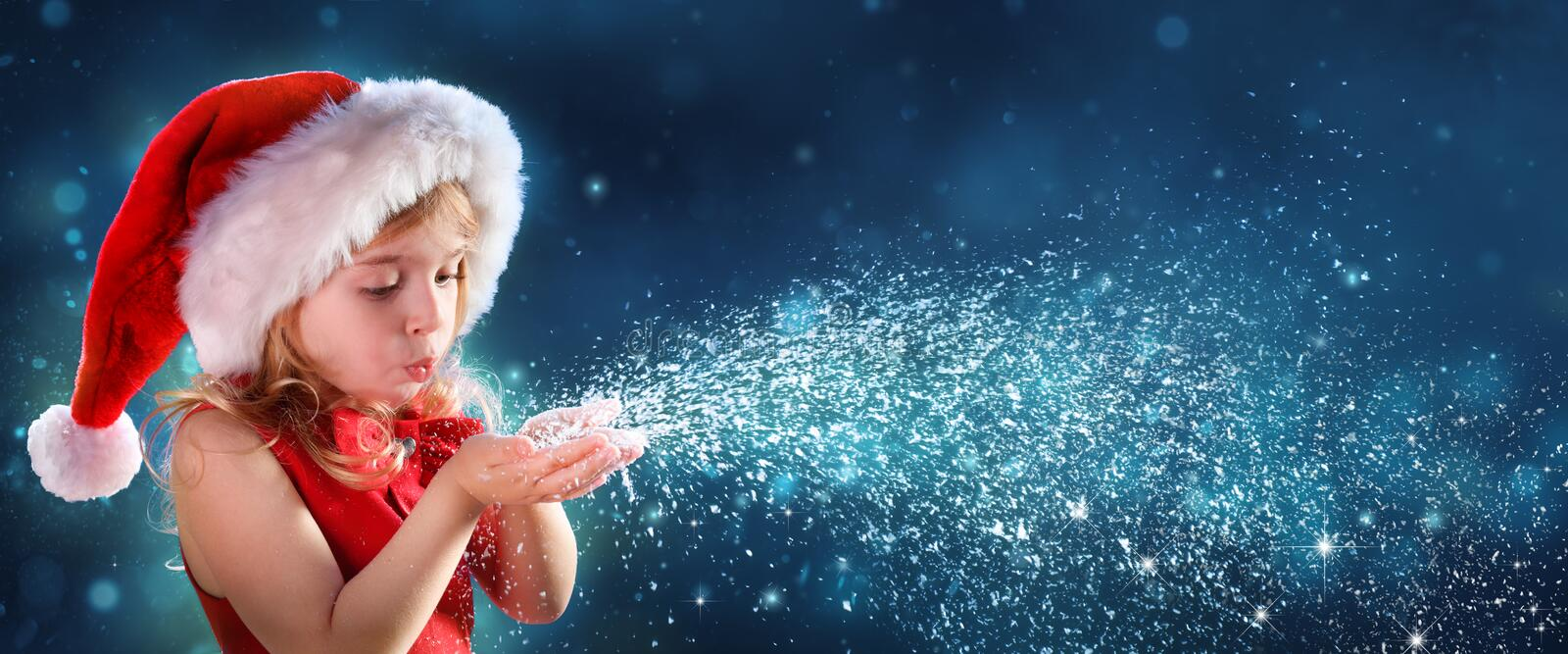Bambina con Santa Hat Blowing Snow fotografie stock