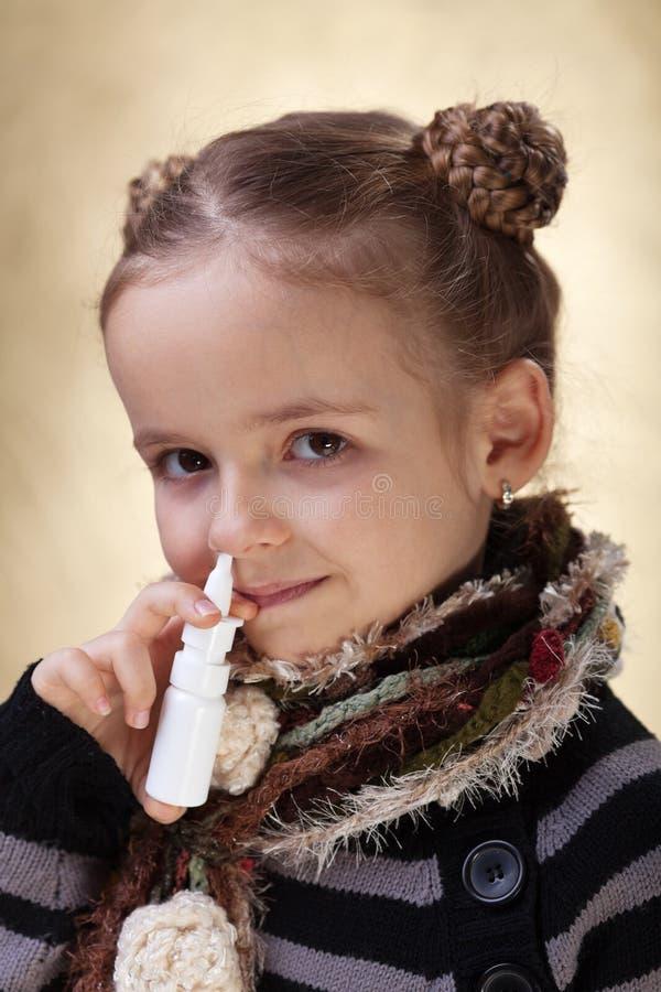 Bambina con spray nasale - combattere l'influenza fotografie stock libere da diritti