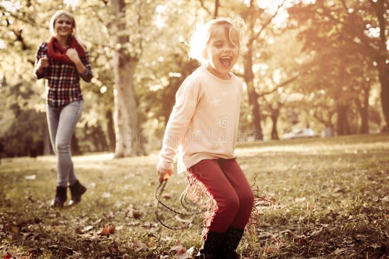 Bambina con sua madre che gioca nel parco fotografia stock libera da diritti