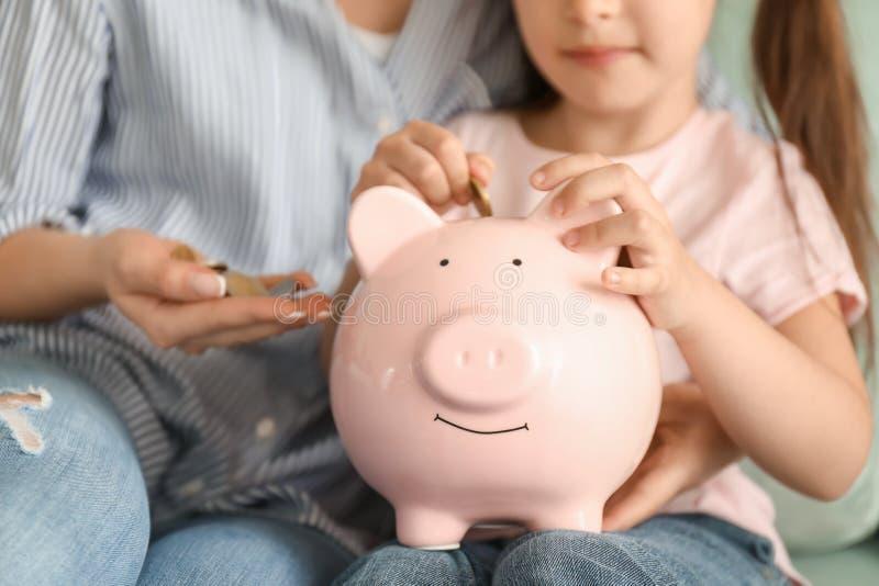 Bambina con sua madre che si siede sul sofà e che mette moneta nel porcellino salvadanaio, primo piano Concetto di risparmio dei  immagini stock