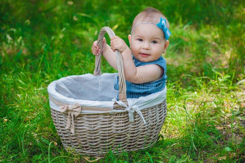 Bambina con un arco blu sulla sua testa che si siede in vimine immagini stock