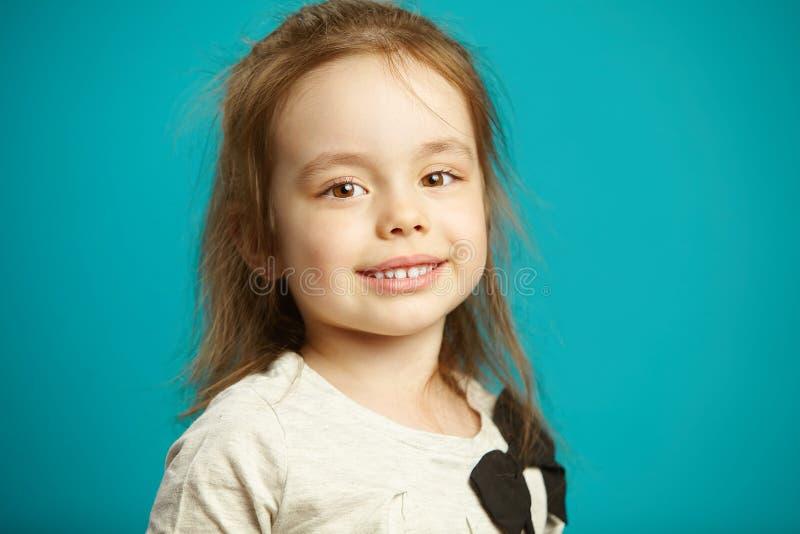 Bambina con un fronte sveglio, bei occhi marroni, supporti bianchi come la neve dei denti su fondo isolato blu immagine stock