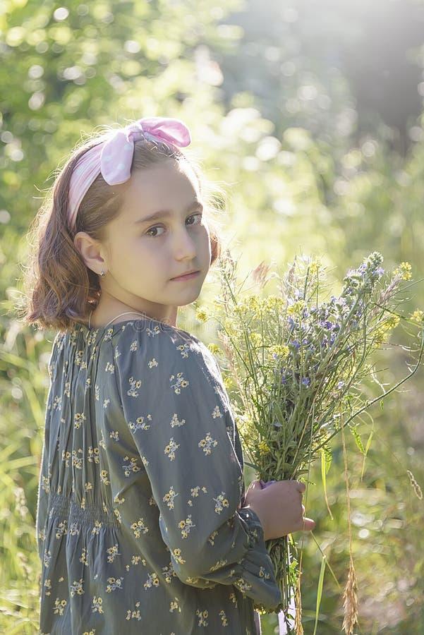 Bambina con un mazzo dei fiori selvaggi, ritratto immagini stock libere da diritti
