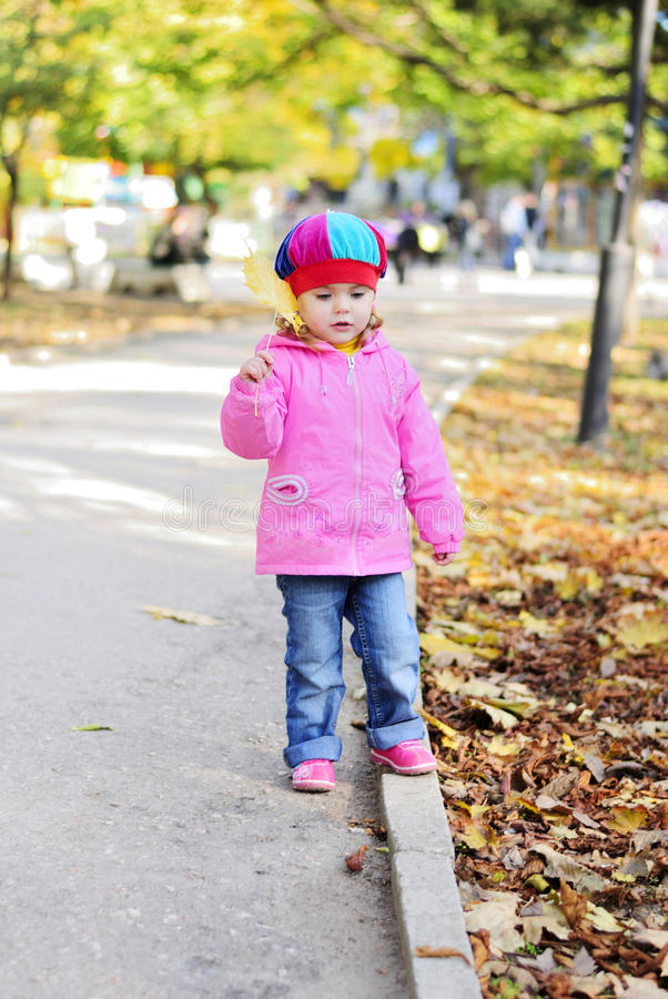 Bambina con un opuscolo giallo nella sosta di autunno immagine stock libera da diritti