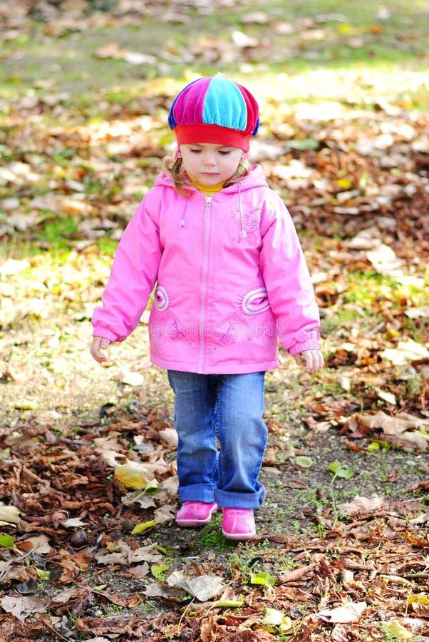 Bambina con un opuscolo giallo nella sosta di autunno fotografia stock