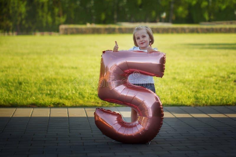 Bambina con un pallone sotto forma di figura cinque Concetto di compleanno immagini stock libere da diritti