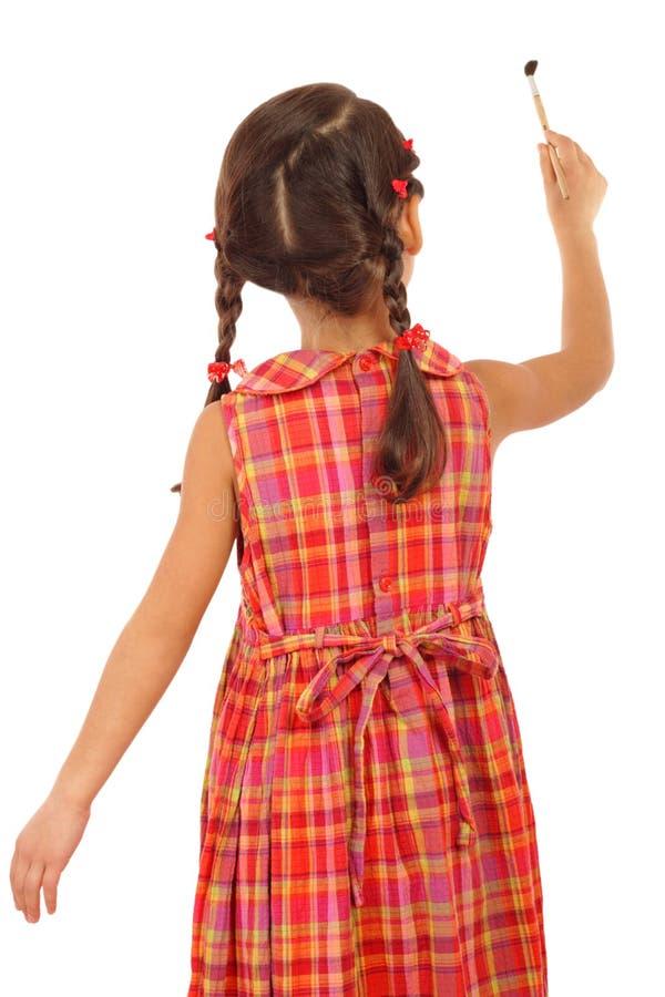 Bambina con un pennello, retrovisione fotografia stock libera da diritti