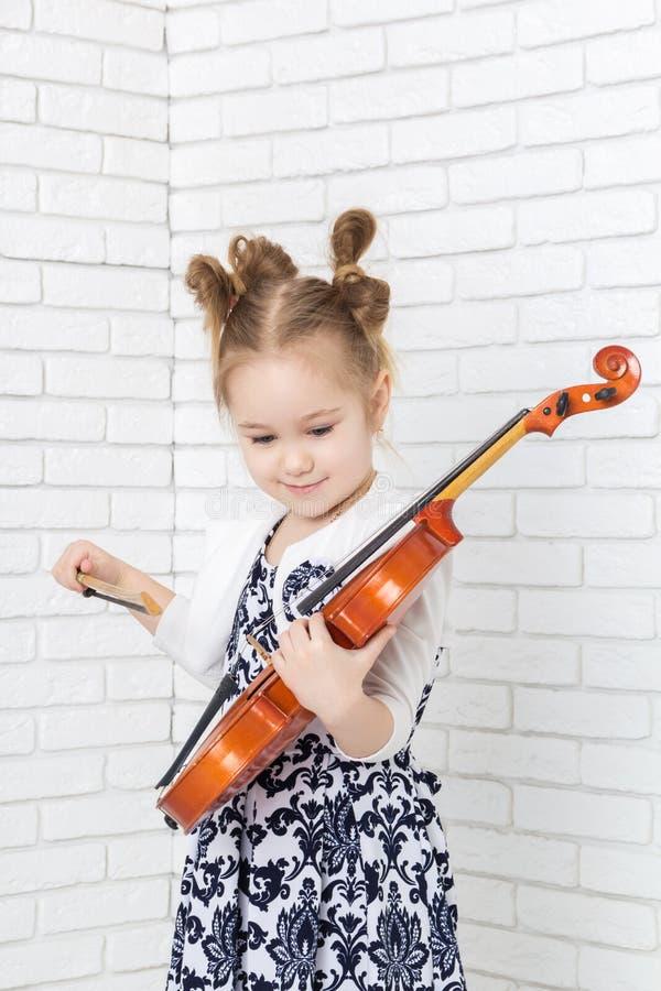Bambina con un violino e un arco fotografia stock libera da diritti