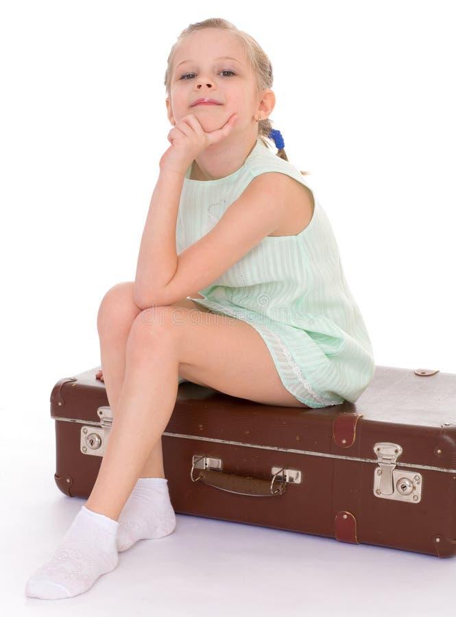 Bambina con una grande e molto vecchia valigia. immagine stock libera da diritti