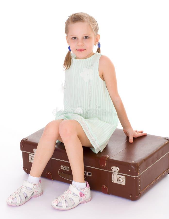 Bambina con una grande e molto vecchia valigia. immagini stock libere da diritti