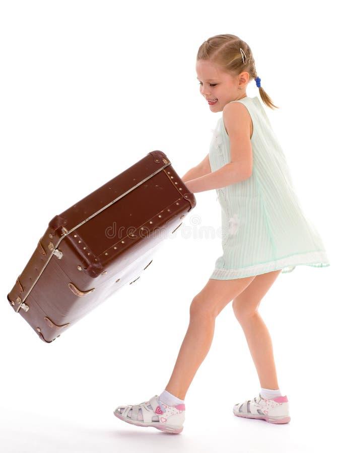 Bambina con una grande e molto vecchia valigia. fotografie stock
