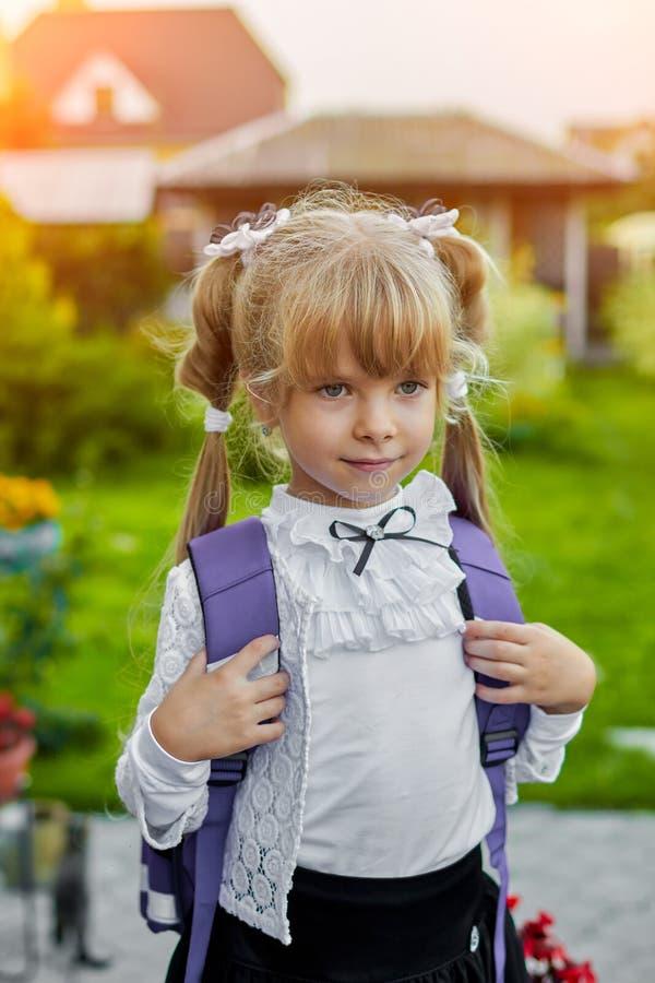 Bambina con uno zaino vicino alla scuola fotografia stock libera da diritti