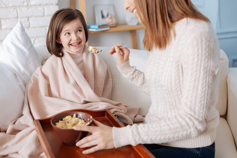 Bambina contentissima che gode della prima colazione con sua madre immagini stock