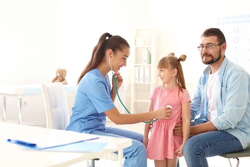 Bambina d'esame del medico dei bambini con lo stetoscopio fotografie stock