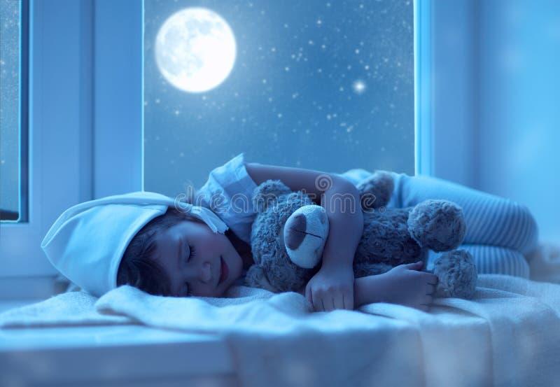 Bambina del bambino che dorme alla finestra che sogna e che ammira la s fotografie stock libere da diritti
