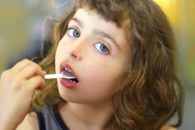 Bambina del Brunette che mangia giocando cucchiaio di plastica fotografia stock libera da diritti