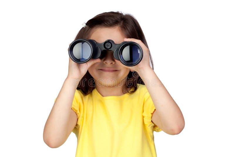 Bambina del Brunette che osserva tramite il binocolo fotografia stock libera da diritti