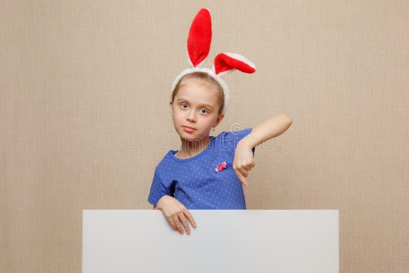 Bambina del coniglietto che indica il suo dito su un'insegna in bianco del Libro Bianco fotografia stock