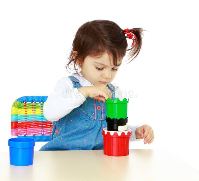 Bambina del primo piano che gioca mentre sedendosi al fotografia stock