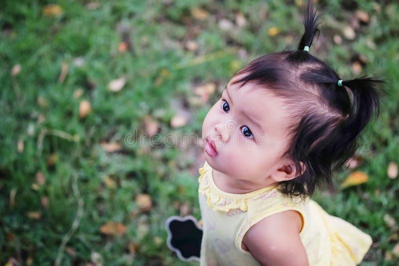 Bambina del primo piano sul pavimento dell'erba e cercare lo spazio dell'immagine nei precedenti di vista del giardino fotografia stock