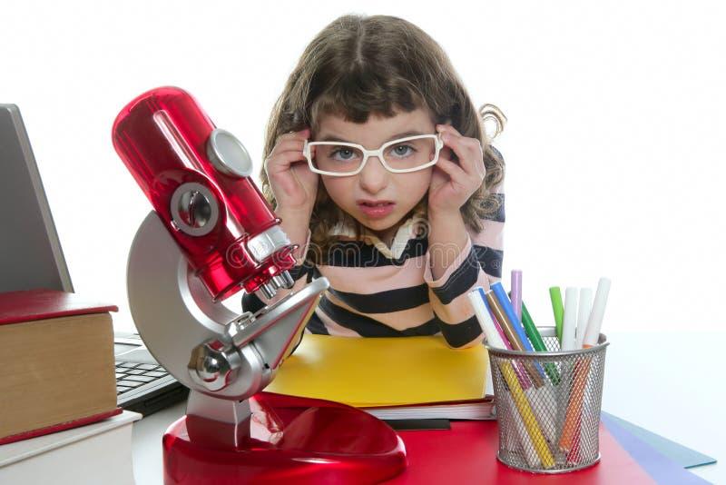 Bambina dell'allievo con il microscopio ed il computer portatile fotografie stock libere da diritti