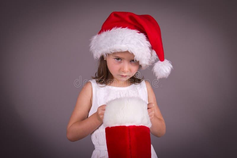 Bambina deludente con il suo immagazzinamento di Natale immagine stock