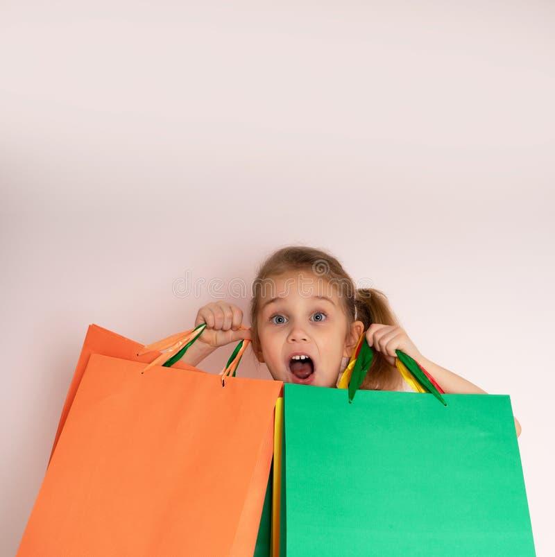Bambina di acquisto che tiene i sacchetti della spesa che rispettano il lato sul fondo del ligth allo spazio della copia fotografia stock libera da diritti