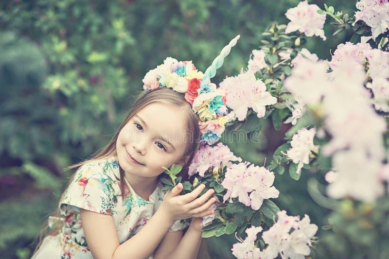 Bambina di fantasia con il corno dell'unicorno dell'arcobaleno con i fiori nel parco dell'azalea Per Halloween fotografia stock