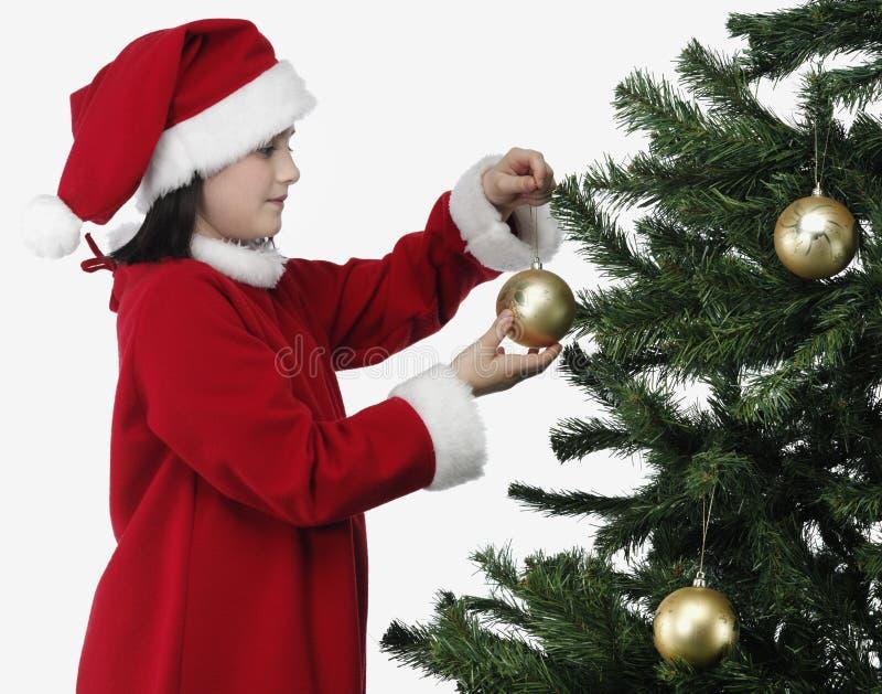 Bambina di natale che decora l'albero di natale fotografia stock