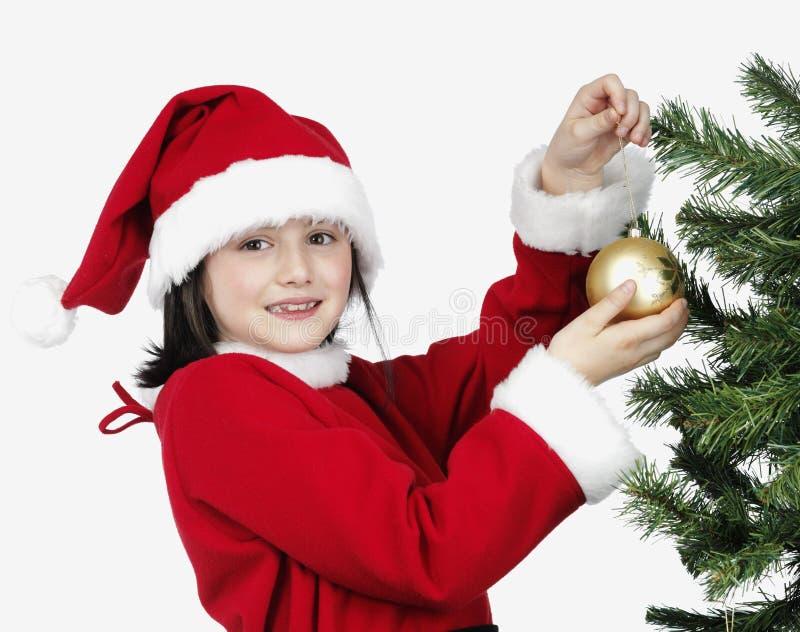Bambina di natale che decora l'albero di natale fotografia stock libera da diritti