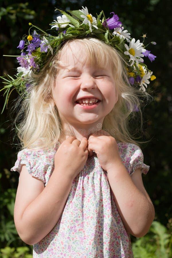 Bambina di risata in corona dei fiori immagini stock libere da diritti