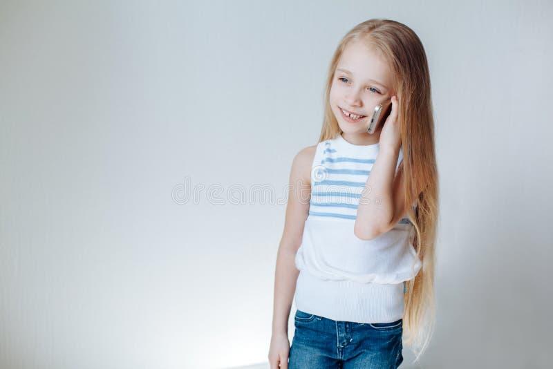 Bambina di risata felice in jeans e maglietta bianca che parla sullo smartphone, guardante da parte, fondo bianco Copi lo spazio fotografia stock libera da diritti