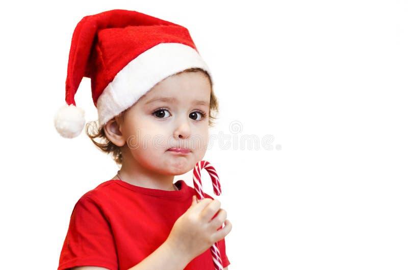 Bambina di santa rossa che tiene in mano il bastone di caramella natalizio il bambino mangia lollipop con appetito, piacere conce fotografie stock libere da diritti