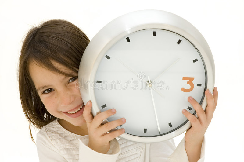 Bambina dietro un orologio fotografia stock
