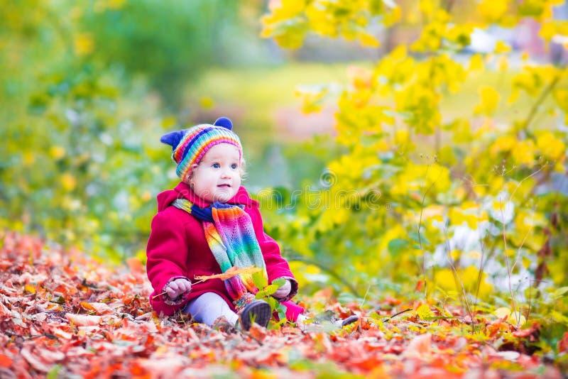 Bambina divertendosi in un parco di autunno immagine stock libera da diritti