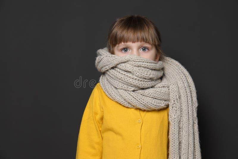 Bambina divertente avvolta in sciarpa contro fondo scuro Precauzione di tosse immagini stock