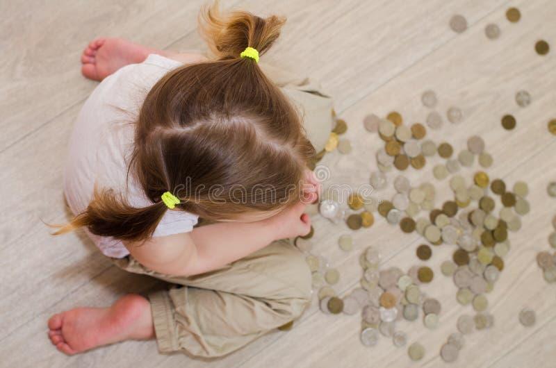 Bambina divertente che conta le monete fotografia stock