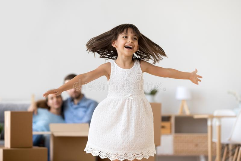 Bambina divertente che gioca salto godendo del muoversi nella nuova casa fotografia stock libera da diritti