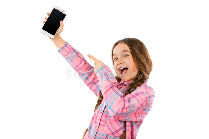 Bambina divertente che mostra Smart Phone con lo schermo in bianco isolato su fondo bianco Giocare e video dell'orologio immagini stock