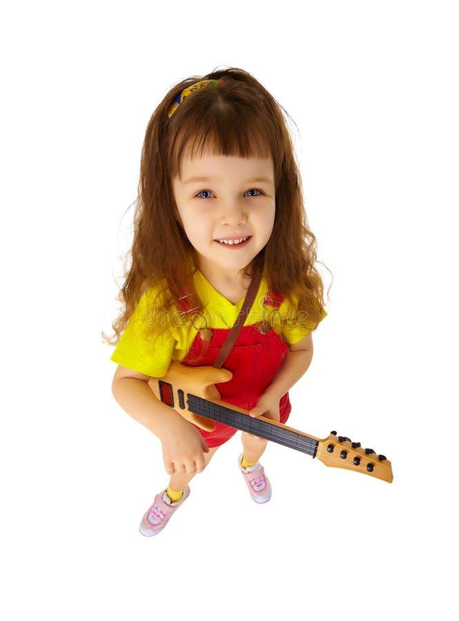 Bambina divertente con la chitarra del giocattolo su bianco immagini stock